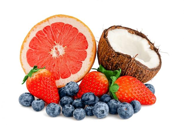 Rozsypisko różne świeże jagody i owoc odizolowywający na biel ścianie.