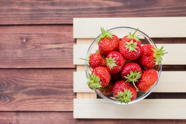 Rozsypisko świeże truskawki w pucharze na białym drewnianym tle. pojęcie organicznych jagód i żywienia. jest bogaty w przeciwutleniacz, mączkę organicznych truskawek. świeżo zebrane owoce. świeże lato