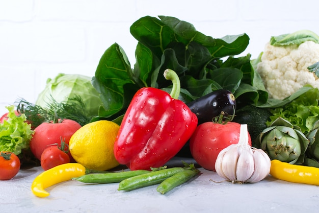 Rozsypisko świezi owoc i warzywo na drewnianym tle. bok choy papryka kapusta zielona karczoch cukinia ogórek pomidor czosnek