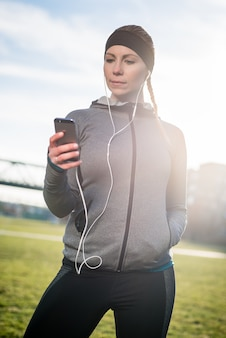 Rozważna młoda kobieta słucha muzyka podczas gdy będący ubranym modnego s