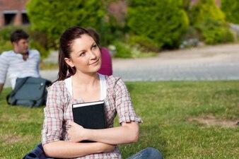 Rozważny żeński uczeń czyta książkowego obsiadanie na trawie
