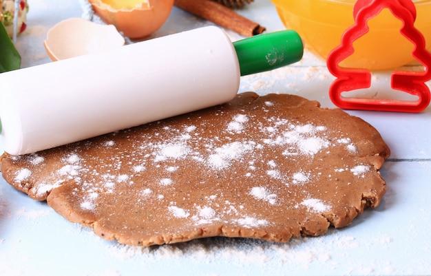 Rozwałkowany ciasto na świąteczne pierniczki domowej roboty na jasnym drewnianym tle rustykalnym selektywnym miękkim stylu rustykalnym
