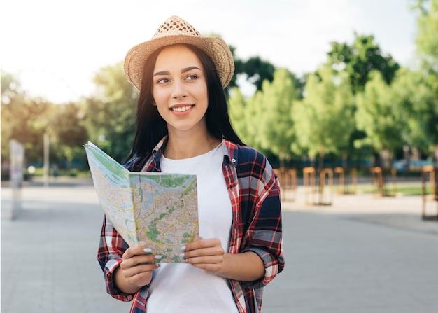 Rozważać młodą uśmiechniętą kobiety mienia mapę na ulicie