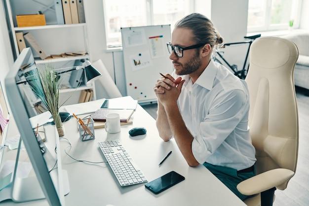 Rozważając następny krok. widok z góry na rozważny młody człowiek w koszuli, pracujący przy użyciu komputera, siedząc w biurze