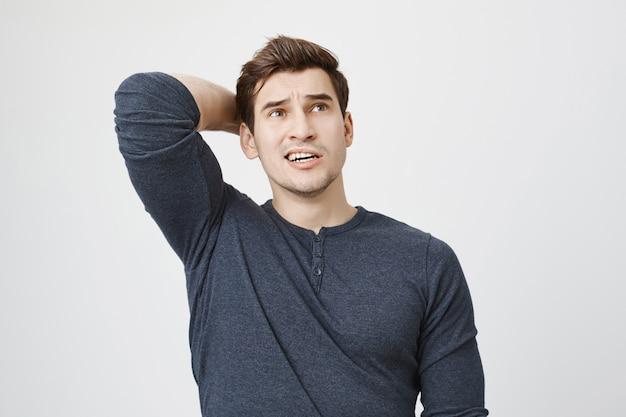 Rozważając zaniepokojony mężczyzna myślący, podrapać się po głowie niezdecydowany