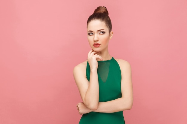 Rozważająca kobieta myśląca, dotykająca podbródka, patrząca w górę. koncepcja ekspresji emocji i uczuć. strzał studio, na białym tle na różowym tle