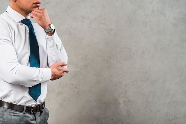 Rozważający młody biznesmen w formalwear pozyci przeciw szarej betonowej ścianie