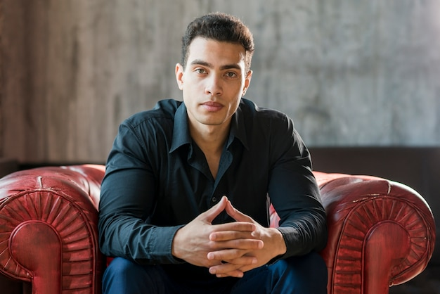 Rozważany młody człowiek siedzi na czerwonym fotelu z ręką splecioną na ścianie