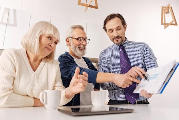 Rozważenie wariantów inwestycji. doświadczony, pozytywny, uroczy spotkanie pośrednika ze starzejącą się parą klientów podczas prezentacji umowy na inwestycję w dom i wyrażania radości