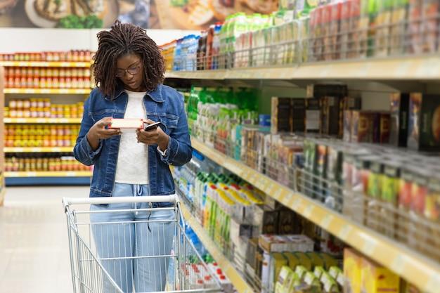 Rozważna amerykanin afrykańskiego pochodzenia kobieta robi zakupy przy sklepem spożywczym