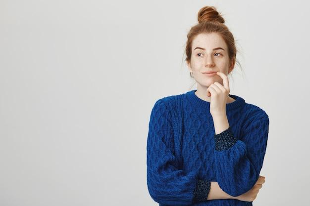 Rozważna atrakcyjna ruda kobieta myśli i wygląda zaintrygowana