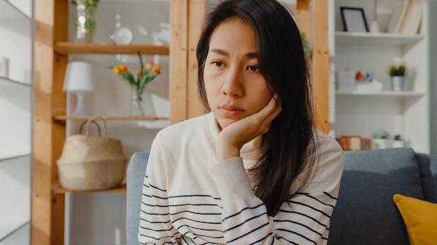 Rozważna azjatka siedzi samotnie, czuje się przygnębiona i spędza samotnie czas w domu
