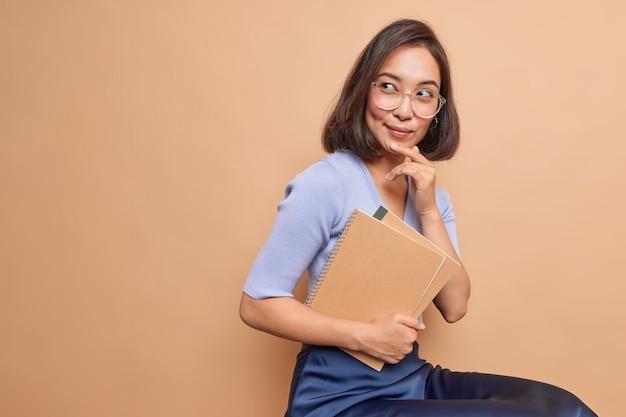 Rozważna azjatycka uczennica nosi spiralne zeszyty wraca do szkoły myśli, jak poszerzyć swoją wiedzę, nosi okulary zwykłe ubrania, siedzi w pomieszczeniu, pusta kopia miejsca na beżowej ścianie