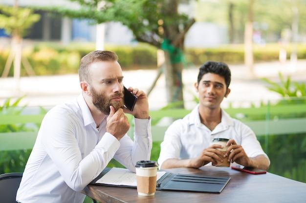 Rozważna biznesmen nacieranie broda podczas gdy opowiadający na telefonie