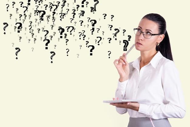 Rozważna biznesowa kobieta w okularach na tle ściany ze znakami zapytania. koncepcja decyzji i wątpliwości. skopiuj miejsce. zdjęcie wysokiej jakości