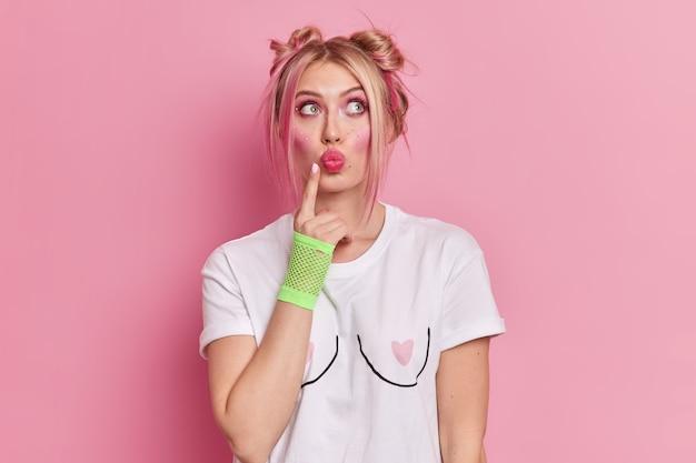 Rozważna blondynka, młoda kobieta z zamyślonymi ustami, ma jasny, żywy makijaż