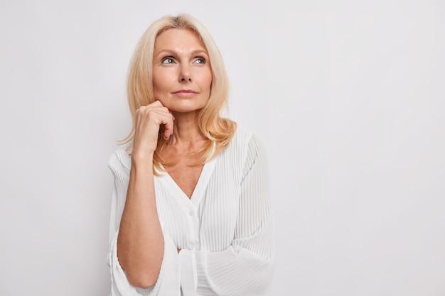 Rozważna blondynka w średnim wieku zastanawia się nad czymś trzyma rękę blisko twarzy ma zdrową skórę minimalny makijaż sprawia, że wybór nosi białą bluzkę pozuje wewnątrz puste miejsce na promocję