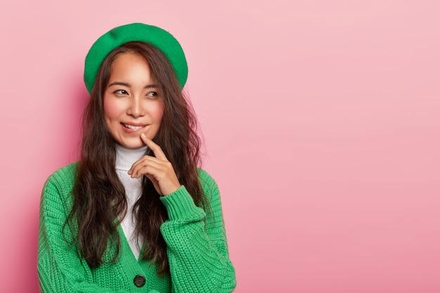 Rozważna brunetka nosi zielony beret i sweter, przygryza usta, patrzy na bok, próbuje podjąć decyzję