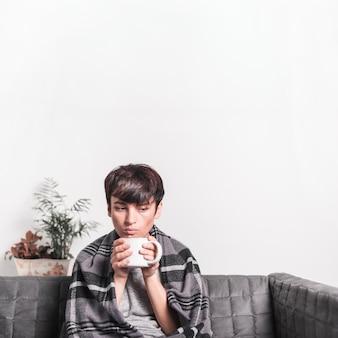 Rozważna chora kobieta z kawowym kubkiem trzyma koc