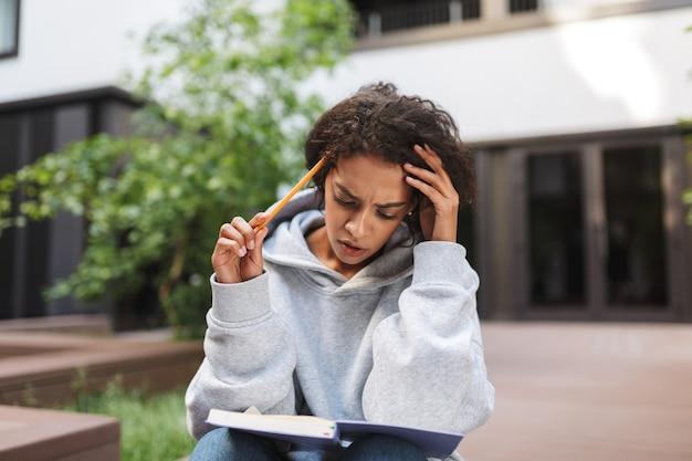 Rozważna dama o ciemnych, kręconych włosach siedząca z notatnikiem na kolanach i ołówkiem w dłoni, przygotowując się do lekcji na dziedzińcu uniwersytetu
