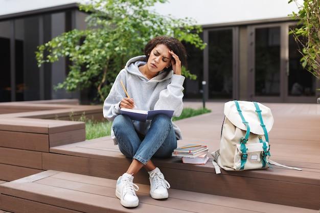 Rozważna dama o ciemnych, kręconych włosach siedząca z notatnikiem na kolanach i ołówkiem w dłoni, przygotowująca się do egzaminów na dziedzińcu uniwersytetu