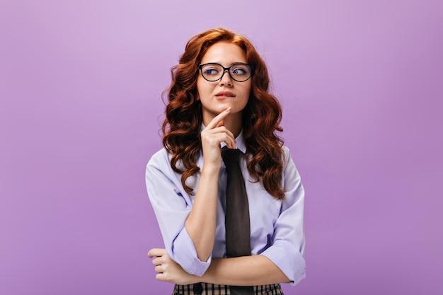 Rozważna dama w koszuli i okularach pozuje na fioletowej ścianie
