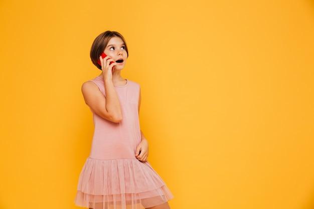 Rozważna dziewczyna przyglądająca przy kopii przestrzenią up i opowiadający na smartphone odizolowywającym