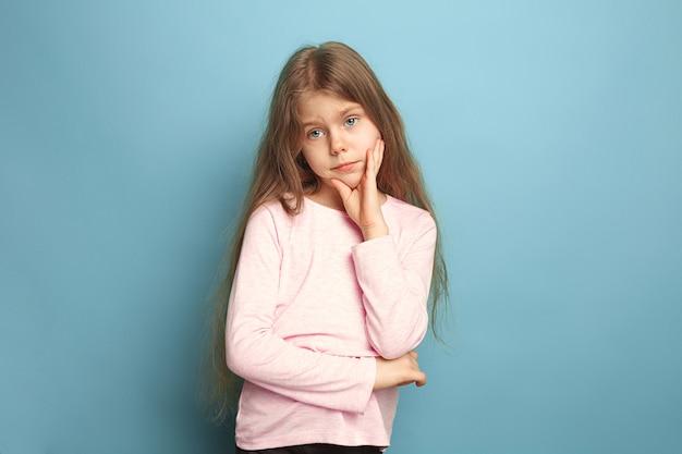 Rozważna dziewczyna. smutna dziewczyna nastolatka na niebieskim studio