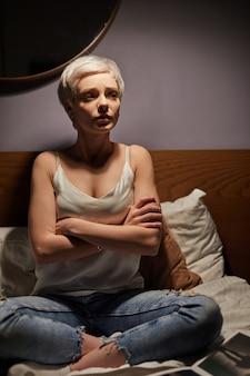 Rozważna i nerwowa kobieta siedząca w nocy w łóżku z założonymi rękoma, cierpiąca na depresję, w rozpaczy, martwi się problemami życiowymi. samotność, niepokój
