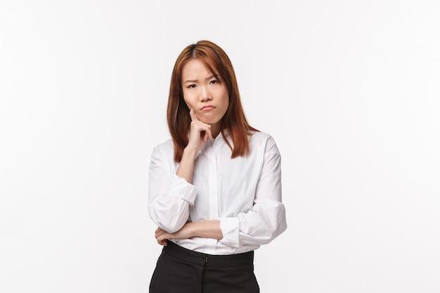Rozważna i poważna zrzędliwa młoda azjatka myśli, mająca problemy z planem makijażu, pochyla się, marszczy brwi i wpatruje się zirytowana, obrażona lub zakłopotana