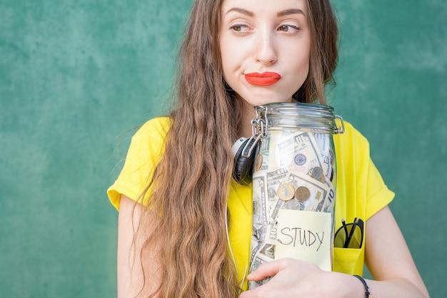 Rozważna i smutna kobieta w żółtej koszulce trzymająca butelkę z oszczędnościami na studia