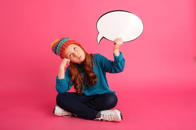 Rozważna imbirowa dziewczyna przyglądająca up i trzyma bąbel mowę odizolowywająca