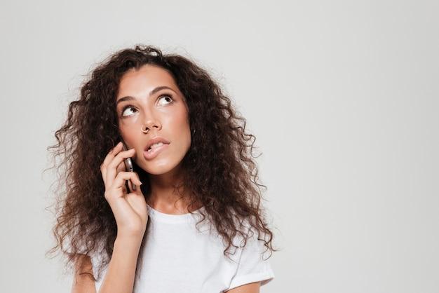 Rozważna kędzierzawa kobieta opowiada smartphone i patrzeje w górę