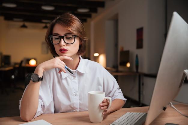 Rozważna kobieta biurowa w okularach.