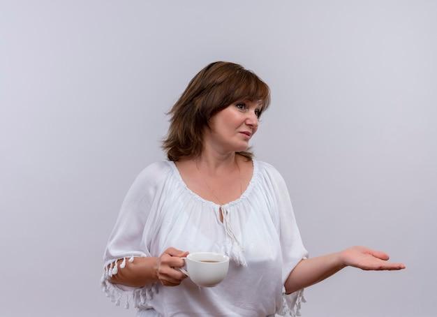 Rozważna kobieta w średnim wieku, trzymając filiżankę herbaty i kładąc rękę na boku na odizolowanej białej ścianie