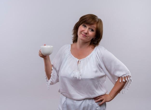 Rozważna kobieta w średnim wieku, trzymając filiżankę herbaty i kładąc rękę na talii na odosobnionej białej ścianie