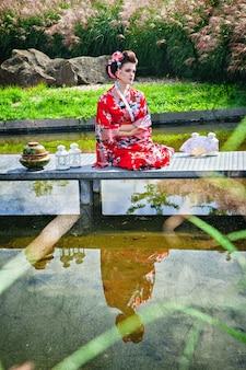 Rozważna kobieta w stroju gejszy w ogrodzie na moście