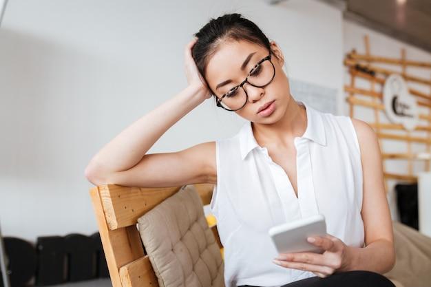 Rozważna kobieta w szkłach używać telefon komórkowego i główkowanie