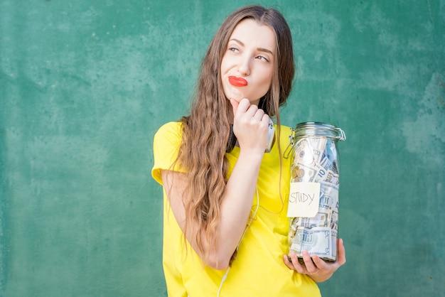 Rozważna kobieta w żółtej koszulce trzymająca butelkę z oszczędnościami na studia