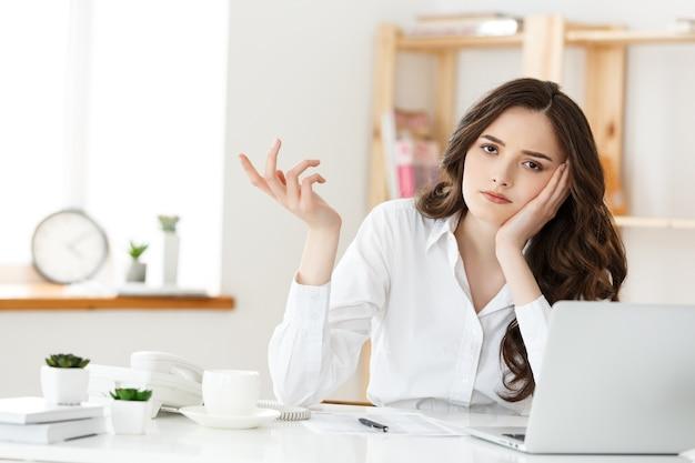 Rozważna kobieta z ręką pod brodą znudzona w pracy, odwracająca wzrok siedząca przy laptopie, zdemotywowany pracownik biurowy odczuwa brak inspiracji, brak motywacji.