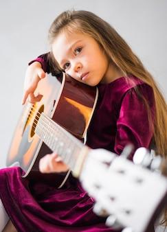 Rozważna mała dziewczynka bawić się gitarę akustyczną
