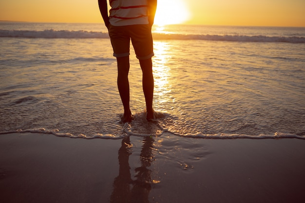 Rozważna mężczyzna pozycja z rękami w kieszeni na plaży