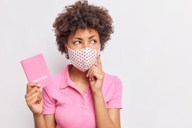 Rozważna młoda afro amerykanka myśli o tym, gdzie mieć wakacje trzyma paszport, nosi maskę ochronną ubraną w różową koszulkę na białym tle nad białą ścianą
