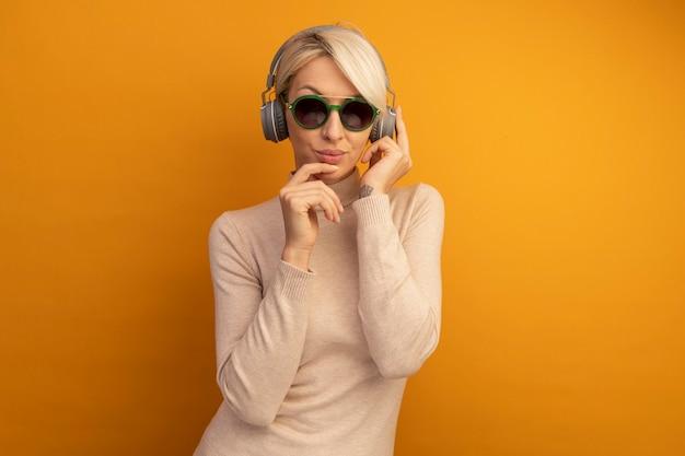 Rozważna młoda blondynka w okularach przeciwsłonecznych i słuchawkach, chwytająca słuchawki dotykające podbródka