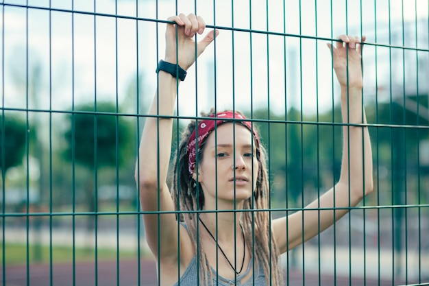 Rozważna młoda dama z dredami stojąca na boisku sportowym i kładąca dwie ręce na płocie z ogniw łańcucha