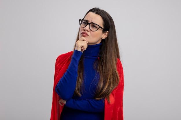 Rozważna młoda dziewczyna superbohatera, patrząc na bok w okularach, kładąc rękę na brodzie na białym tle