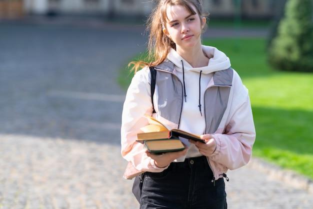 Rozważna młoda kobieta niosąca książki w dłoniach