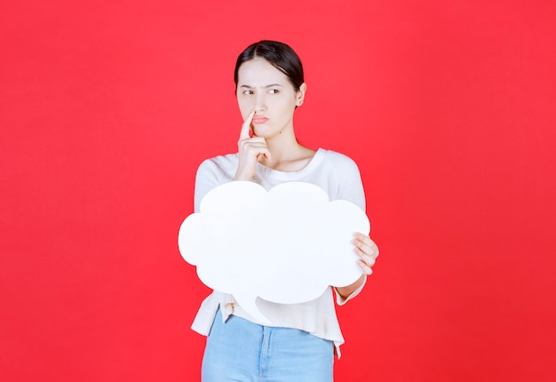 Rozważna młoda kobieta trzyma tablicę pomysłów w kształcie chmury