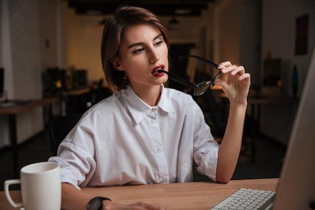 Rozważna młoda kobieta trzymająca okulary i myśląca w biurze