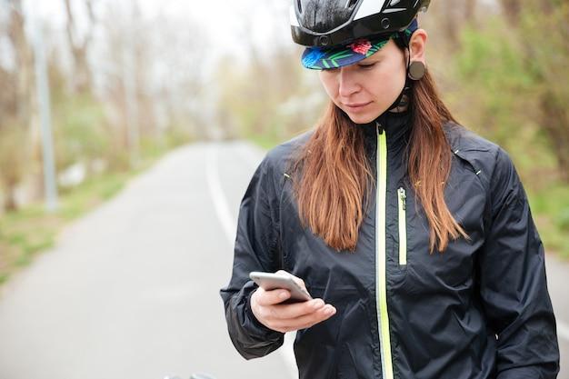 Rozważna młoda kobieta w kasku rowerowym przy użyciu telefonu komórkowego w parku